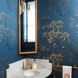 Imagen de aseo clásico, pequeño, con puertas de armario negras, paredes azules, lavabo bajoencimera, encimera de mármol y encimeras blancas