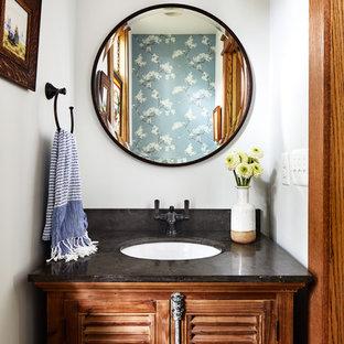 Exemple d'un WC et toilettes craftsman de taille moyenne avec un placard à porte persienne, des portes de placard en bois brun, un mur blanc, un sol en bois brun, un lavabo encastré, un plan de toilette en quartz modifié, un sol marron et un plan de toilette marron.