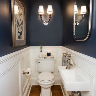 Small transitional medium tone wood floor and brown floor powder room photo in Philadelphia with a two-piece toilet, blue walls and a wall-mount sink