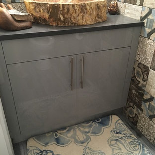 Photo of a medium sized mediterranean cloakroom in Miami with flat-panel cabinets, grey cabinets, a two-piece toilet, multi-coloured tiles, cement tiles, multi-coloured walls, medium hardwood flooring, a vessel sink, solid surface worktops, grey floors and grey worktops.