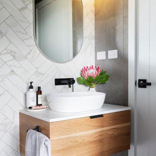 Idee per un piccolo bagno di servizio moderno con ante in legno scuro, WC monopezzo, pistrelle in bianco e nero, piastrelle in gres porcellanato, pareti bianche, pavimento in gres porcellanato, lavabo a bacinella, top in quarzo composito, pavimento grigio e top bianco