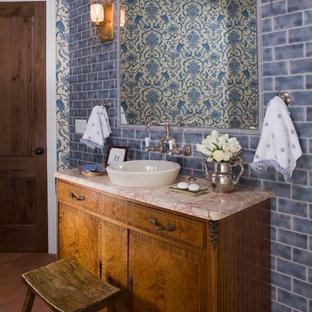 Idées déco pour un WC et toilettes méditerranéen avec une vasque, des portes de placard en bois brun, un carrelage bleu et un carrelage métro.