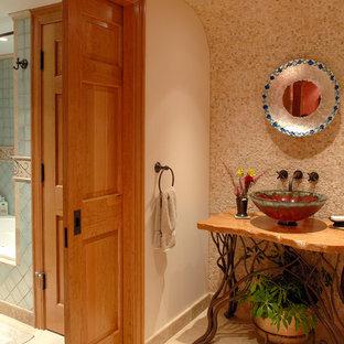 Cette photo montre un WC et toilettes chic avec une vasque, un plan de toilette en bois, un carrelage beige, un mur beige, un sol en travertin, des dalles de pierre et un plan de toilette marron.