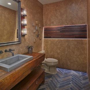 На фото: туалет в стиле фьюжн с фасадами островного типа, фасадами цвета дерева среднего тона, коричневыми стенами, накладной раковиной, столешницей из дерева, коричневым полом и коричневой столешницей с