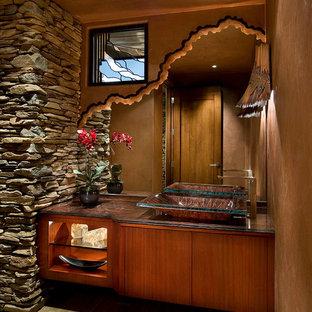 Diseño de aseo actual, grande, con lavabo sobreencimera, armarios tipo mueble, puertas de armario de madera oscura, suelo de travertino, paredes marrones, encimera de granito y encimeras marrones