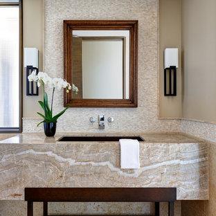 На фото: класса люкс большие туалеты в стиле современная классика с бежевыми фасадами, унитазом-моноблоком, разноцветной плиткой, керамической плиткой, бежевыми стенами, полом из известняка, врезной раковиной, столешницей из гранита, бежевым полом и бежевой столешницей