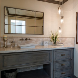 Design ideas for a medium sized traditional cloakroom in Phoenix with raised-panel cabinets, medium wood cabinets, a one-piece toilet, multi-coloured tiles, stone tiles, beige walls, a vessel sink, quartz worktops and cement flooring.