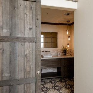 Idée de décoration pour un WC et toilettes tradition de taille moyenne avec un placard avec porte à panneau surélevé, des portes de placard en bois brun, un WC à poser, un carrelage multicolore, un carrelage de pierre, un mur beige, une vasque, un plan de toilette en quartz et un sol en carreaux de ciment.