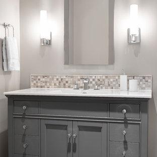 Immagine di un piccolo bagno di servizio tradizionale con lavabo integrato, ante con riquadro incassato, ante grigie, top in quarzo composito, piastrelle grigie, piastrelle a mosaico, pareti grigie, pavimento in legno massello medio e top bianco