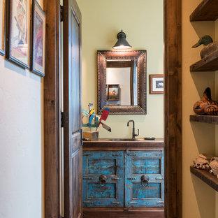 Ispirazione per un bagno di servizio american style con ante con finitura invecchiata, pavimento in legno massello medio, lavabo da incasso, top in legno e top marrone