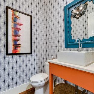Imagen de aseo actual con armarios tipo mueble, puertas de armario naranjas, paredes multicolor, suelo de madera oscura, lavabo sobreencimera, suelo marrón y encimeras blancas
