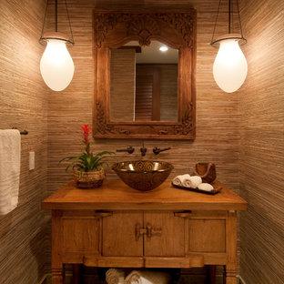 ハワイのトロピカルスタイルのおしゃれなトイレ・洗面所 (ベッセル式洗面器、家具調キャビネット、中間色木目調キャビネット、茶色い壁) の写真