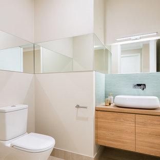Идея дизайна: туалет среднего размера в современном стиле с фасадами островного типа, светлыми деревянными фасадами, унитазом-моноблоком, синей плиткой, керамической плиткой, бежевыми стенами, полом из цементной плитки, настольной раковиной, столешницей из ламината и бежевым полом