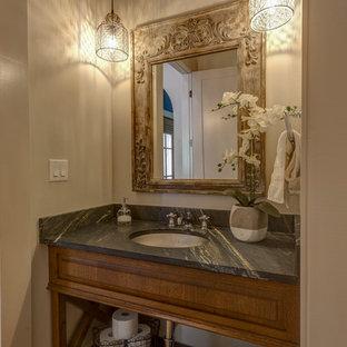 Réalisation d'un WC et toilettes champêtre de taille moyenne avec un placard en trompe-l'oeil, des portes de placard en bois brun, un WC séparé, un mur blanc, béton au sol, un lavabo encastré, un plan de toilette en stéatite, un plan de toilette noir et un sol beige.