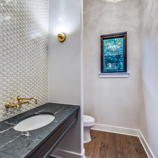 Photo of a medium sized traditional cloakroom in Austin with freestanding cabinets, grey cabinets, multi-coloured tiles, ceramic tiles, grey walls, light hardwood flooring, a submerged sink, soapstone worktops, brown floors and a one-piece toilet.