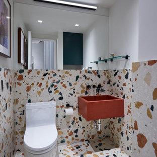 ニューヨークの小さいコンテンポラリースタイルのおしゃれなトイレ・洗面所 (一体型トイレ、マルチカラーのタイル、石スラブタイル、白い壁、テラゾーの床、一体型シンク、人工大理石カウンター、マルチカラーの床、赤い洗面カウンター) の写真