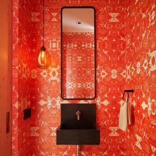Cette image montre un WC et toilettes minimaliste avec un mur rouge et un lavabo suspendu.