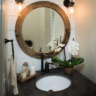 Aménagement d'un WC et toilettes bord de mer de taille moyenne avec un placard à porte persienne, des portes de placard en bois sombre, un lavabo encastré et un plan de toilette en béton.