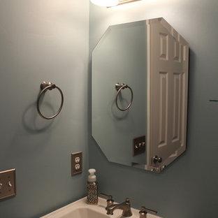 На фото: туалет в классическом стиле с унитазом-моноблоком, синими стенами, бежевым полом и полом из ламината с