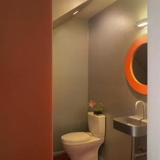Idee per un bagno di servizio minimal con lavabo sospeso e pavimento rosso