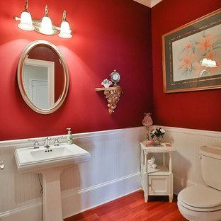 Diseño de aseo tradicional, grande, con lavabo con pedestal, sanitario de dos piezas, paredes rojas, suelo de madera en tonos medios y suelo marrón