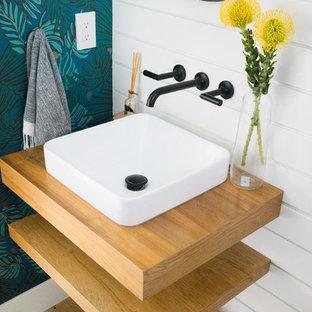 Ejemplo de aseo vintage, de tamaño medio, con puertas de armario de madera clara, paredes blancas, suelo de madera clara, lavabo sobreencimera y encimera de madera