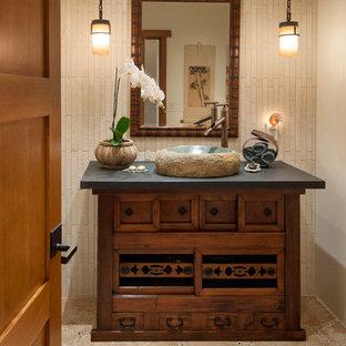 Diseño de aseo asiático, de tamaño medio, con lavabo sobreencimera, armarios tipo mueble, encimera de granito, baldosas y/o azulejos beige, paredes beige, suelo de travertino y puertas de armario de madera en tonos medios