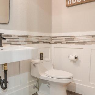 Esempio di un bagno di servizio moderno di medie dimensioni con ante lisce, ante bianche, piastrelle grigie, piastrelle di vetro, pareti grigie, pavimento in laminato, lavabo sospeso, top in quarzo composito, pavimento grigio e top bianco