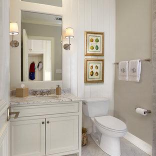 Cette photo montre un petit WC et toilettes nature avec un lavabo encastré, des portes de placard blanches, un plan de toilette en marbre, un WC séparé, un mur gris, un sol en marbre, un placard avec porte à panneau encastré, un sol gris et un plan de toilette blanc.