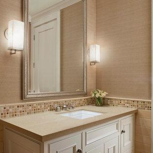 Réalisation d'un grand WC et toilettes champêtre avec des portes de placard blanches, un WC à poser, un carrelage beige, un carrelage de pierre, un mur beige, un sol en carrelage de céramique, un plan de toilette en surface solide, un lavabo encastré, un placard avec porte à panneau encastré, un sol beige et un plan de toilette beige.