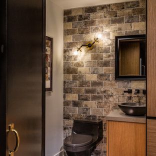 This is an example of a small urban cloakroom in Las Vegas with flat-panel cabinets, medium wood cabinets, a one-piece toilet, multi-coloured tiles, porcelain tiles, white walls, vinyl flooring, a vessel sink, quartz worktops, brown floors and grey worktops.
