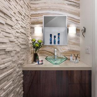 Idées déco pour un petit WC et toilettes contemporain avec un placard à porte plane, des portes de placard en bois sombre, un carrelage beige, une vasque, un sol gris, un plan de toilette beige et un mur beige.