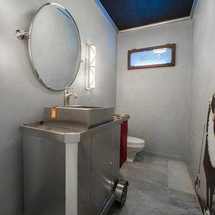 Immagine di un bagno di servizio bohémian di medie dimensioni con lavabo a bacinella, consolle stile comò, top in acciaio inossidabile, WC monopezzo, piastrelle grigie, pareti grigie e pavimento in marmo