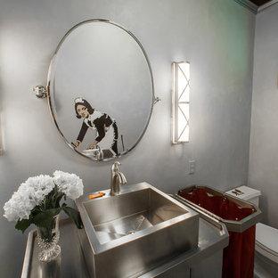 ヒューストンの中くらいのエクレクティックスタイルのおしゃれなトイレ・洗面所 (ベッセル式洗面器、家具調キャビネット、一体型トイレ、グレーのタイル、グレーの壁、ステンレスの洗面台) の写真