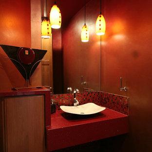 Ispirazione per un bagno di servizio minimal di medie dimensioni con ante in legno scuro, piastrelle rosse, pareti rosse, parquet scuro, lavabo a bacinella, top in superficie solida e top rosso