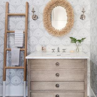 Cette photo montre un WC et toilettes bord de mer de taille moyenne avec un placard à porte plane, des portes de placard en bois clair, un WC séparé, un mur gris, un sol en travertin, un lavabo encastré, un plan de toilette en marbre, un sol gris et un plan de toilette blanc.