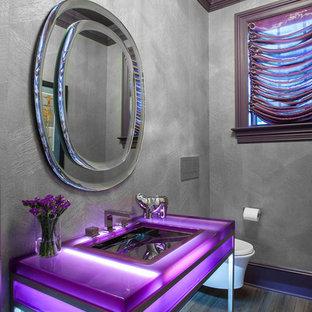 ニューヨークの中くらいのコンテンポラリースタイルのおしゃれなトイレ・洗面所 (壁掛け式トイレ、グレーの壁、濃色無垢フローリング、コンソール型シンク、茶色い床、紫の洗面カウンター) の写真