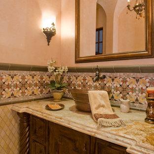 На фото: класса люкс огромные туалеты в средиземноморском стиле с фасадами с утопленной филенкой, коричневыми фасадами, унитазом-моноблоком, разноцветной плиткой, плиткой мозаикой, бежевыми стенами, настольной раковиной, столешницей из кварцита и разноцветной столешницей