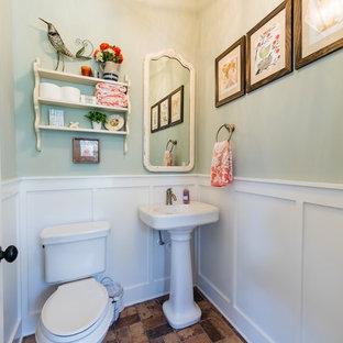 Cette image montre un grand WC et toilettes rustique avec un WC séparé, un mur vert, un sol en brique, un lavabo de ferme et un sol multicolore.