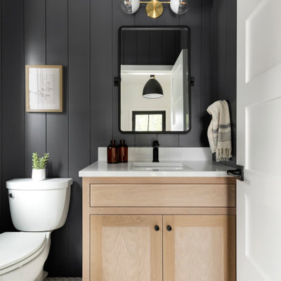 Inspiration for a transitional mosaic tile floor, white floor and shiplap wall powder room remodel in Minneapolis with shaker cabinets, light wood cabinets, a two-piece toilet, black walls, an undermount sink, white countertops and a built-in vanity