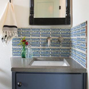 Aménagement d'un petit WC et toilettes campagne avec un placard à porte plane, des portes de placard bleues, un carrelage bleu, des carreaux de céramique, un mur blanc, un lavabo encastré, un plan de toilette en béton et un plan de toilette gris.