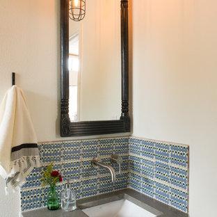 Immagine di un piccolo bagno di servizio country con ante lisce, ante blu, piastrelle blu, piastrelle in ceramica, pareti bianche, lavabo sottopiano, top in cemento e top grigio