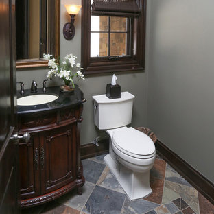 Small traditional cloakroom in Detroit with freestanding cabinets, dark wood cabinets, grey walls, slate flooring and solid surface worktops.