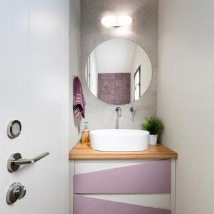 テルアビブの小さいコンテンポラリースタイルのおしゃれなトイレ・洗面所 (フラットパネル扉のキャビネット、紫のキャビネット、グレーのタイル、磁器タイル、グレーの壁、磁器タイルの床、ベッセル式洗面器、木製洗面台、グレーの床、ベージュのカウンター) の写真