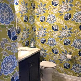 Idee per un piccolo bagno di servizio classico con ante in stile shaker, ante blu, WC a due pezzi, pareti multicolore, lavabo sottopiano, top in granito, pavimento in vinile e pavimento bianco