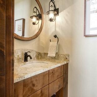 ソルトレイクシティの大きいラスティックスタイルのおしゃれなトイレ・洗面所 (フラットパネル扉のキャビネット、中間色木目調キャビネット、ベージュの壁、淡色無垢フローリング、アンダーカウンター洗面器、御影石の洗面台) の写真