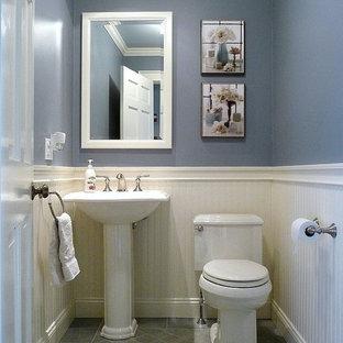 Foto på ett litet vintage toalett, med ett piedestal handfat, en toalettstol med separat cisternkåpa, blå väggar, klinkergolv i porslin och grå kakel