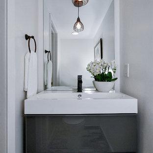 Réalisation d'un WC et toilettes urbain avec un placard à porte plane et des portes de placard grises.