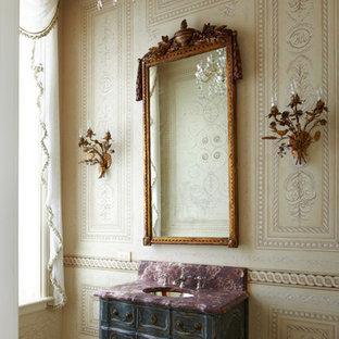На фото: туалеты в викторианском стиле с врезной раковиной, фасадами островного типа, бежевыми стенами, искусственно-состаренными фасадами и фиолетовой столешницей
