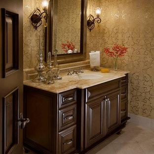 フェニックスの小さいトラディショナルスタイルのおしゃれなトイレ・洗面所 (家具調キャビネット、茶色いキャビネット、ベージュの壁、トラバーチンの床、アンダーカウンター洗面器、大理石の洗面台) の写真